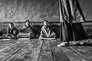 A group of young monks brefly interrupt their prayers while an elder walks by at a Buddhist temple. Paro,  Bhutan