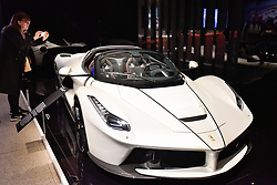 "© Licensed to London News Pictures. 14/11/2017. London, UK.  A visitor views a LaFerrari Aperta, 2017. Preview of ""Ferrari: Under the Skin"", an exhibition at the Design Museum to mark the 70th anniversary of Ferrari.  Over GBP140m worth of Ferraris are on display from private collections including Michael Schumacher's 2000 F1 winning car.  The exhibition runs 15 November to 15 April 2018.  Photo credit: Stephen Chung/LNP"