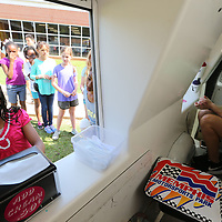 Gabby Griffin, left, 10, selects her flavor for her shaved ice as Angie Moore, right, helps another student at Lawndale Elementary School in Tupelo on Wednesday.