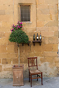 Pienza, Tuscany, Italy wooden chair and wine bottles in front of a home