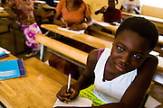 Souga Doupoaka, 12, sits in class at the Youga primary school in the town of Youga, approximately 205 km southeast of Burkina Faso's capital Ouagadougou on Tuesday April 28, 2009. Souga had never gone to school until two years ago, when members of her family started working at the Youga gold mine -  the salaries they receive allows them to pay for Souga's school fees.
