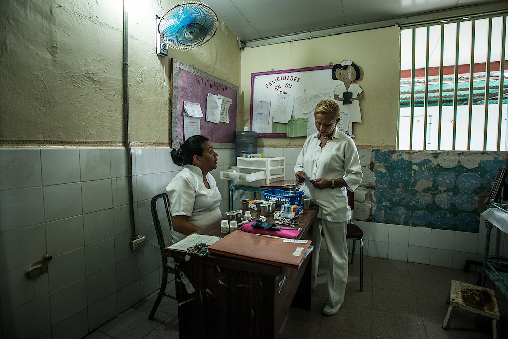 BARQUISIMETO, VENEZUELA - AUGUST 24, 2016: Head nurse, Évila García, (right) debates with other nurses about which patients are the most unstable, to decide which patients will receive the limited number of pills on hand, and which will go without. The hospital has not employed a psychiatrist in over two years, so even though they are not doctors, the nursing staff find themselves responsible for doing a psychiatrist's work - they make decisions about how to medicate patients - modifying doses and swapping one patient's pills to give to another, who might be more unstable and need them more. They reference medical files from two years ago when a licensed psychiatrist was on staff - all written by hand and kept in paper folders. They use a mix of the old treatment plans from two years ago, plus their own observations of the patient, and modify treatments and care based on years of learning from trial and error.   The economic crisis that has left Venezuela with little hard currency has also severely affected its public health system, crippling hospitals like El Pampero Psychiatric Hospital by leaving it without the resources it needs to take care of patients living there. Drugs used to combat bipolar disorder, epilepsy, schizoaffective disorder and chronic anxiety are now in short supply, as are numerous sedatives and tranquilizers needed to care for patients. When a patient loses control, often the only thing they can do is lock them in an isolation cell to prevent them from hurting themselves, other patients and members of the staff.  PHOTO: Meridith Kohut for The New York Times