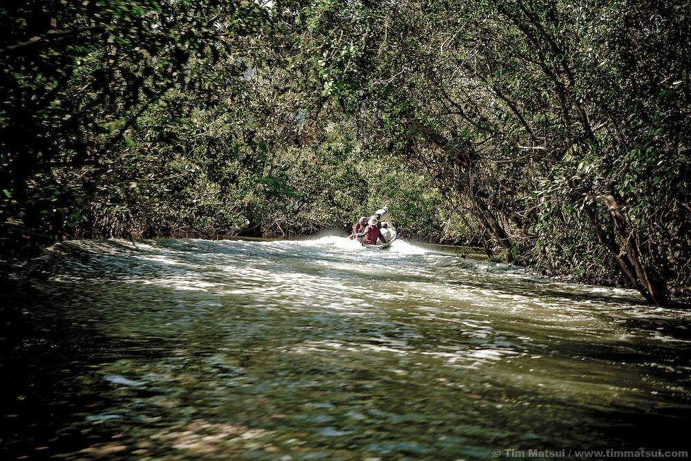 Undocumented migrants with a local boat pilot navigate a river on their way to Kao Wong, an unofficial border crossing watched by Cambodian military police who are largely ex-Khmer Rouge soldiers and Thai army. With land mines planted nearly everywhere, it takes a guide with minefield knowledge and relationships with the border patrol to get migrants into Thailand where they look for jobs. This leaves the migrants vulnerable to some of the well-documented cases of labor and sex abuse at the hands of human traffickers working with some guides.