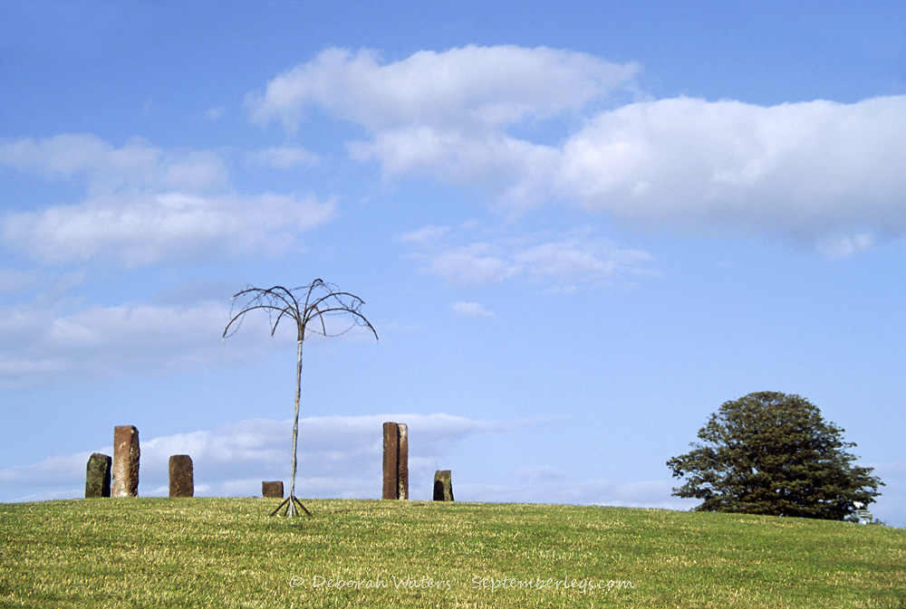 Metal tree sculpture standing before a modern circle of standing stones beneath a blue sky, Solfest, Cumbria, UK 2005