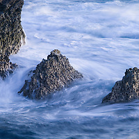 Ocean waves crashing on coastal rocks in very early morning light