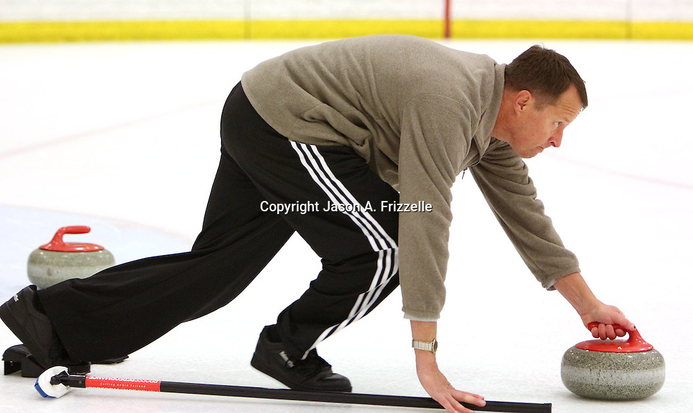 Tony Jacobs delivers a stone during a curling match at the Wilmington Ice House. (Jason A. Frizzelle)