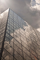 The glass sides of the Louvre Pyramid reflecting the clouds