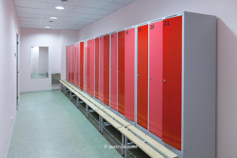 Changing room, locker room with red cupboard doors. Bench seat.  Village school in Metsapoole, Estonia