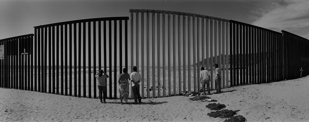 Mexicans look through the U.S.-Mexico border fence into the United States from a Mexican beach west of Tijuana, Mexico..(Credit Image: © Louie Palu/ZUMA Press)