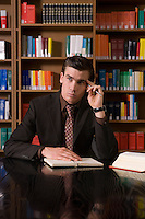 Pensive man wearing suit with book at desk in library