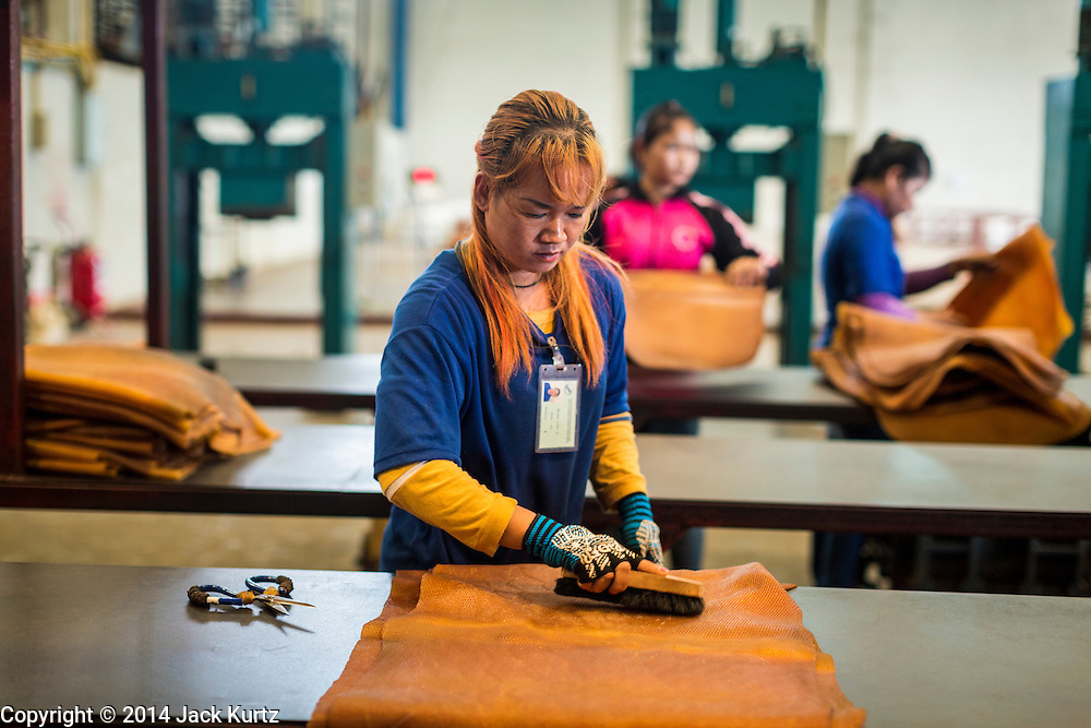 02 SEPTEMBER 2014 - BO THONG, CHONBURI, THAILAND: A worker at Bothong Rubber Fund Cooperative in Bo Thong, Chonburi, Thailand, cuts rubber sheets to size after they were dried in a smoker. Thailand is the leading rubber exporter in the world. In the last two years, the price paid to rubber farmers has plunged from approximately 190 Baht per kilo (about $6.10 US) to 52 Baht per kilo (about $1.60 US). It costs about 65 Baht per kilo to produce rubber ($2.05 US). A rubber farmer in southern Thailand committed suicide over the weekend, allegedly because the low prices meant he couldn't provide for his family. Other rubber farmers have taken jobs in the construction trade or in Bangkok to provide for their families during the slump.    PHOTO BY JACK KURTZ