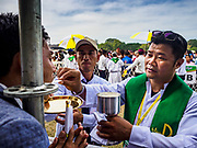 29 NOVEMBER 2017 - YANGON, MYANMAR:  A man hanging from a metal pole accepts communion during the Papal Mass in Yangon. Hundreds of thousands of Catholics from Myanmar attended the mass said by Pope Francis at Kyaikkasan Sports Ground in Yangon Wednesday. Pope Francis is on the first visit by a Pope to Myanmar.   PHOTO BY JACK KURTZ