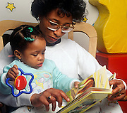 Bedtime story.  Mother reads to daughter.