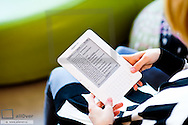 Young woman reading e-book, amazon kindle (model-released)