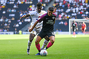 Peterborough United defender Niall Mason (24)battles for possession  with Milton Keynes Dons striker Kieran Agard (14) during the EFL Sky Bet League 1 match between Milton Keynes Dons and Peterborough United at stadium:mk, Milton Keynes, England on 24 August 2019.