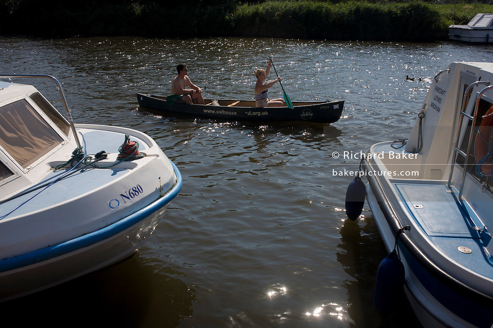 Couple canoeing past motorised boats on the River Bure at Horning on the Norfolk Broads.