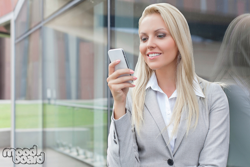 Beautiful young businesswoman text messaging on mobile phone while leaning on glass wall