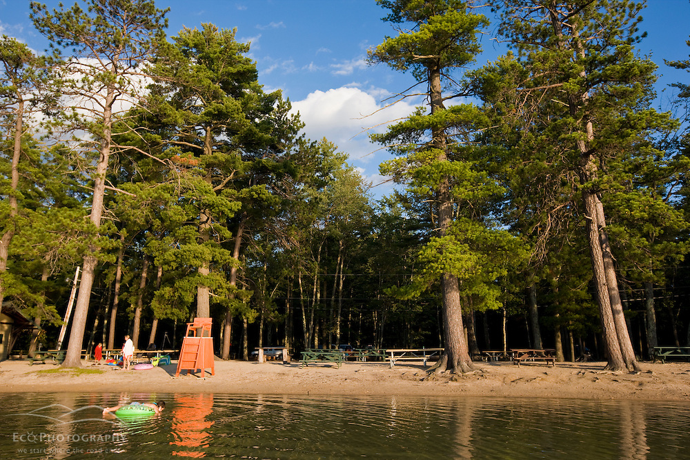 A girl floats at the beach at White Lake State Park in Tamworth, New Hampshire.
