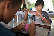 Youths read the instructions on a box of condoms and are taught the importance of the expiration date and how to properly apply the sheath at a two-day training of ethnic Shan youth on HIV/AIDS prevention run at Ban Wiang Wai, Chiang Mai, Thailand on July 16, 2011.