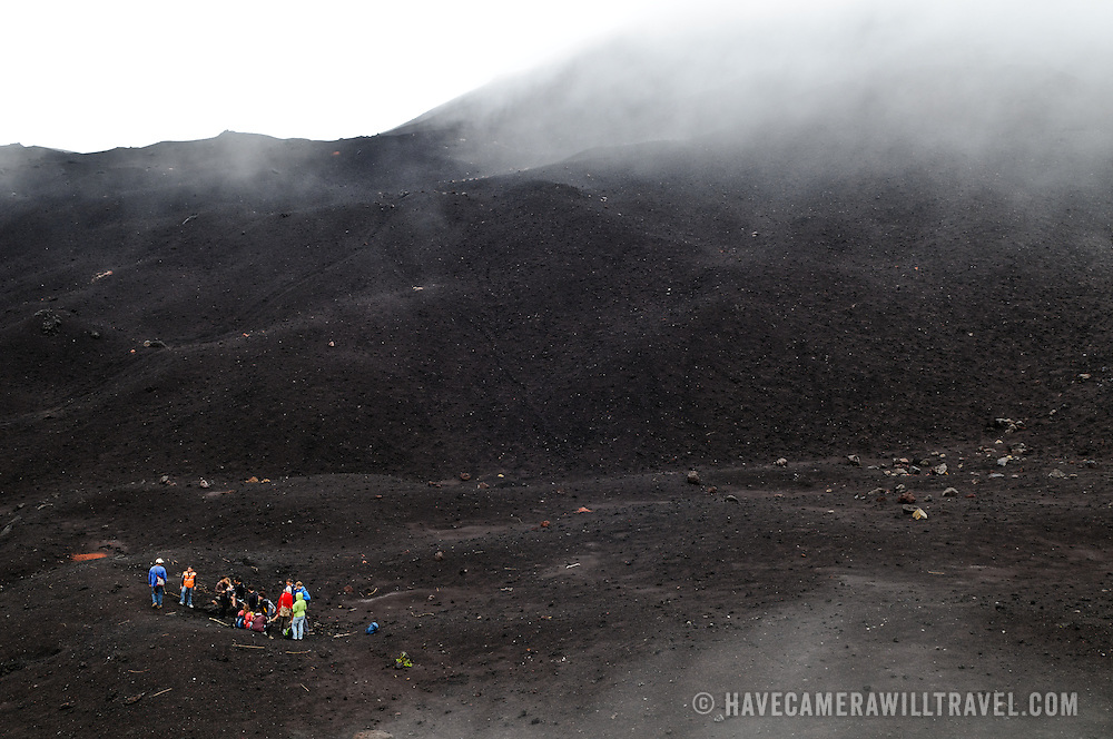 A tour group of hikers at the summit of Pacaya Volcano. Pacaya is an active volcano that forms part of the Central America Volcanic Arc. It forms a popular tourist destination easily accessible from Antigua and Guatemala City. Situated within the Pacaya National Park, it rises to 2,552 metres (8,373 ft). Its last major eruption, which caused considerable damange to nearby villages and reshaped the summit, was in May 2010. That eruption and scattered volcanic ash over much of the nearby area, prompting school closings and emergency evacuations and cleared much of the vegetation near the top of the mountain.