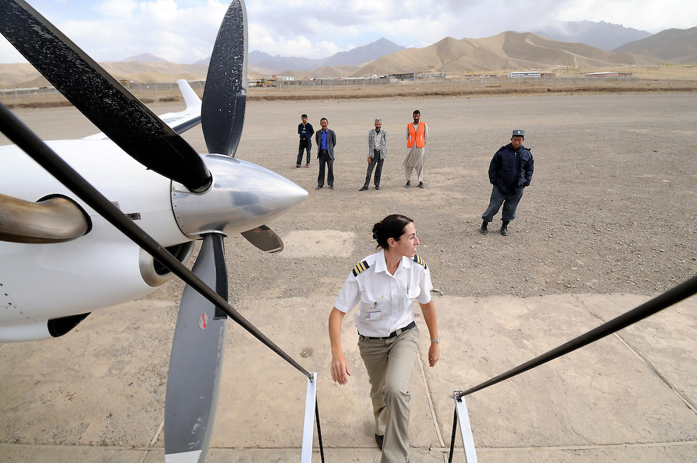 Pilot, Danielle Aitchison, is the last to board the UNHAS flight on the remote Bamiyan air field.  Afghan ground staff and security watch from the background.  The airstrip is made of rocks and gravel and not entirely straight, making take off and landings more challenging in the remote mountins...