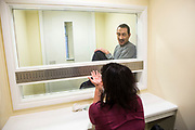 A prisoner on a closed visit sits talking to his wife. Closed visits take place in locked rooms with a toughened glass window between the prisoner and his visitor.  HMP/YOI Portland, Dorset. A resettlement prison with a capacity for 530 prisoners. <br /> © prisonimage.org.  Any image use must be agreed first. All images must be properly credited.