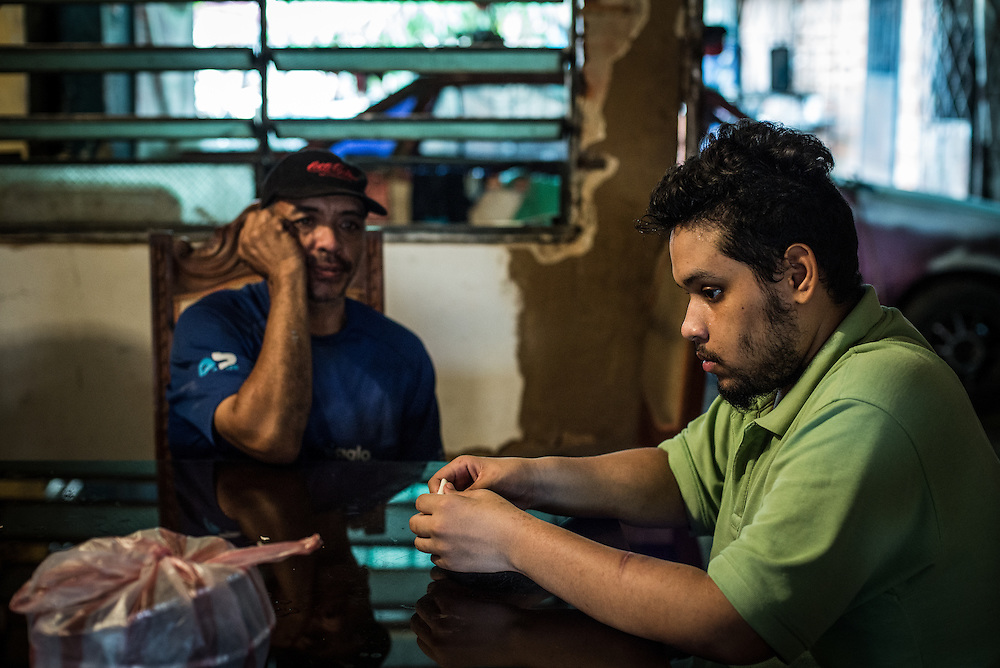 "MARACAY, VENEZUELA - JULY 15, 2016: Schizophrenic Accel Simeone sits in his family's dining room with his father Mario.  When he is unmedicated, Accel is tormented by voices in his head, and believes that his home, especially his bedroom, are full of famous hip hop artists like Nicki Minaj and Ñengo Flow, a Puerto Rican singer, that torment him with insults, and demand he commit acts of violence against himself and his family.  ""They even throw grenades at me,"" he said.  On days when there is enough medicine to clear his mind, Accel helps around the house and can even cook meals by himself.  He likes to draw and writes original hip-hop lyrics. He has written dozens of songs, one about his relationship with his brother Gerardo, who is also schizophrenic. Another, called ""The Lights Are Out,"" tells of the constant blackouts his neighborhood faces.  PHOTO: Meridith Kohut for The New York Times"