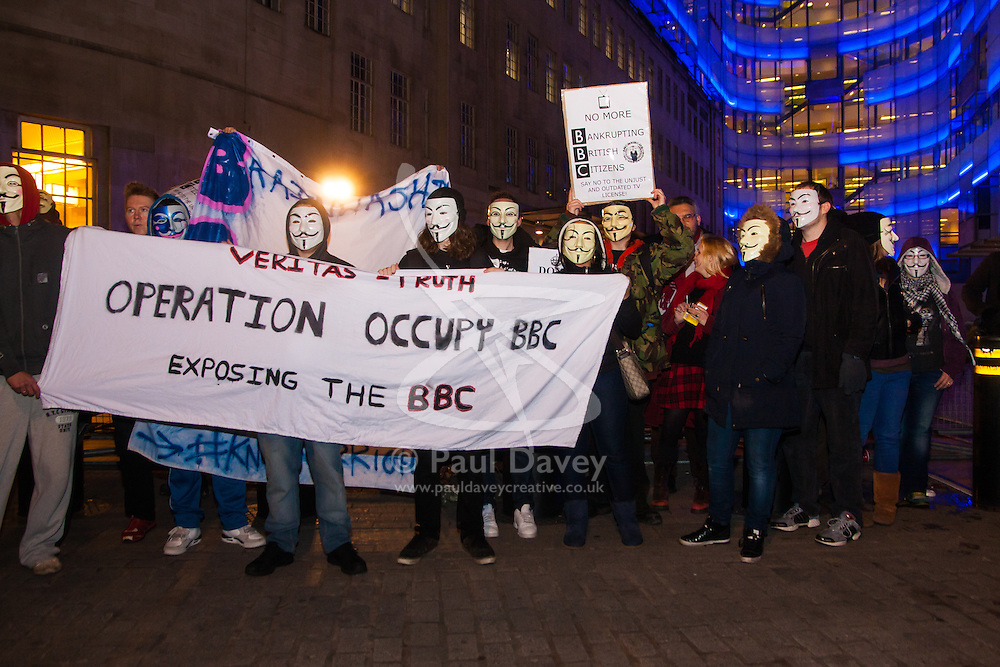 """London, December 23rd 2014. Online activism group Anonymous march through London from the City to the BBC's HQ on Great Portland Street in protest against alleged biases and coverups of a """"paedophile ring"""". PICTURED: The small group of protesters pose for a group shot outside the BBC"""