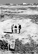 Three managers consulting plans of a new factory in the desert. They stand among piles of bricks.  In the distance, a factory complex already build gleams faintly.