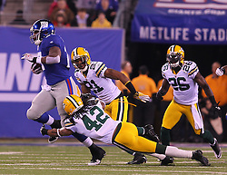 Dec 4, 2011; East Rutherford, NJ, USA; New York Giants running back Brandon Jacobs (27) is tackled by Green Bay Packers free safety Morgan Burnett (42) during the first half at MetLife Stadium.