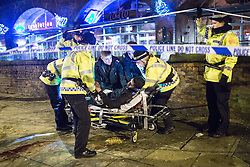 "© Licensed to London News Pictures . 20/12/2014 . Manchester , UK . Paramedics and police lift a man with a head injury on to a trolley outside Deansgate Locks nightclub venue . The ambulance took over 40 minutes to arrive . "" Mad Friday "" revellers out in the rain and cold in Manchester . Mad Friday is typically the busiest day of the year for emergency services , taking place on the last Friday before Christmas when office Christmas parties and Christmas revellers enjoy a night out .  Photo credit : Joel Goodman/LNP"