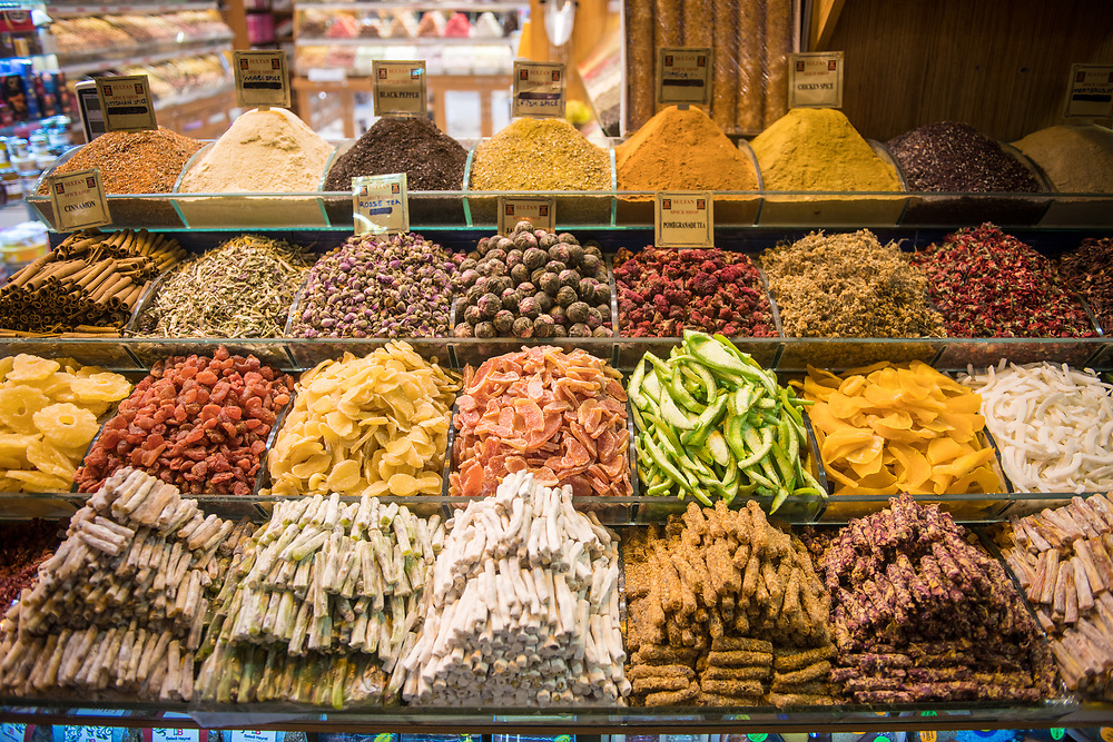 Orderly piles of various dried fruits, spices and other goods <br /> on display in market stall at Istanbul Spice bazaar in Turkey