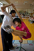 Cao Xiaoli, a professional acrobat, practices balancing on one hand in the practice room at Shanghai Circus World in Shanghai, China.  (Featured in the book What I Eat: Around the World in 80 Diets.) The caloric value of her day's worth of food on a typical day in June was 1700 kcals.  She is 16 years of age; 5 feet, 2 inches tall; and 99 pounds.  Cao Xiaoli lives in  a room with nine other girls. She started her career as a child, performing with a regional troupe in her home province of Anhui. Now she practices five hours a day, attends school with the other members of her troupe, and performs seven days a week. She says what she likes best about being an acrobat is the crowd's reaction when she does something seemingly dangerous.