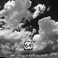 a road sign for highway 64 junction between angel fire and taos new mexico with cloudscape creates notions of environmental and travel contrast.