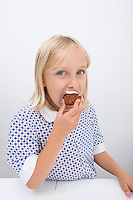 Portrait of cute girl eating muffin at table in house