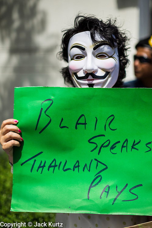 "27 AUGUST 2013 - BANGKOK, THAILAND: A Thai ""White Mask"" protester holds up a sign protesting against the fee allegedly paid to Tony Blair to bring him to speak in Thailand. About 25 people, including at least two British citizens, picketed the British embassy in Bangkok Tuesday morning. They were protesting against former British Prime Minister Tony Blair, who is expected to speak to a political reform commission established by Thai Prime Minister Yingluck Shinawatra. The protest leaders were invited in to the Embassy grounds to speak to representative of the British government. The protest disbanded afterwards. No one was arrested during the protest, which lasted a little over an hour. The Thai government has denied paying Blair his usual fee of about $800,000 (US).        PHOTO BY JACK KURTZ"