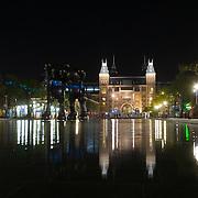 NLD/Amsterdam/20150513 - Rijksmuseum  Amsterdam bij nacht gezien vanaf de bijver met daarin de ART Zuid 2015 kunstwerken van Brian Donnely, als artiest bekend onder de naam KAWS