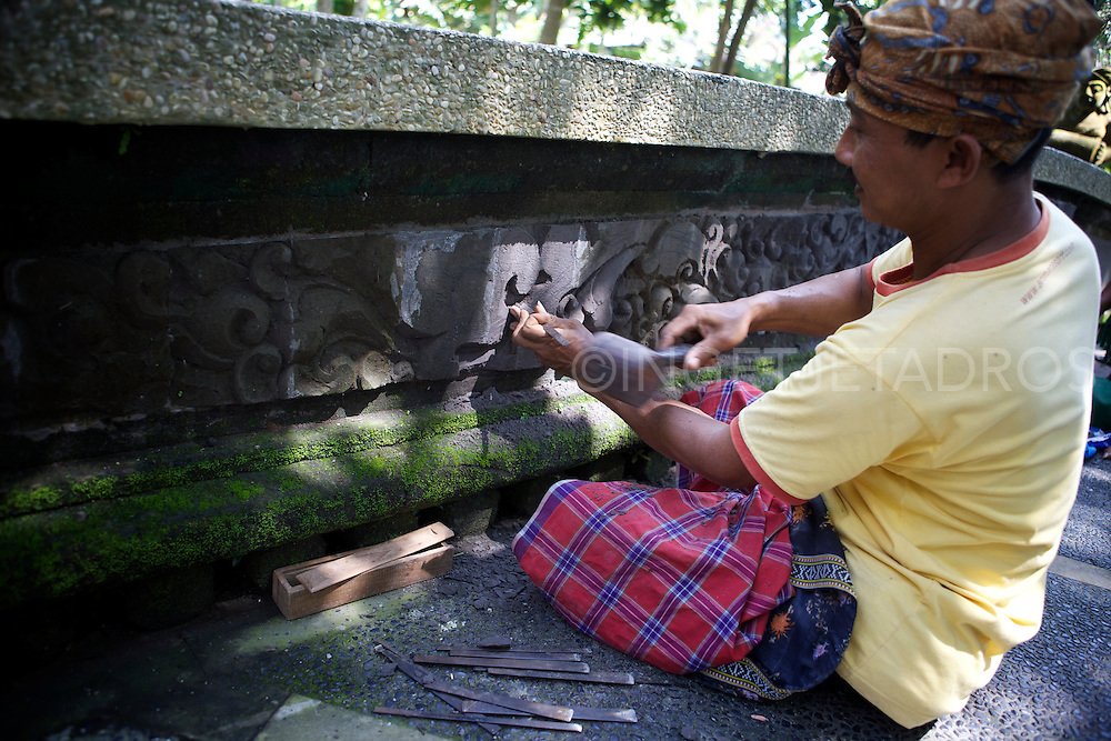 A local Ubud craftsman carving the fresh cement on the side of a bridge at the Arma Resort in Ubud.<br /> &copy;Ingetje Tadros