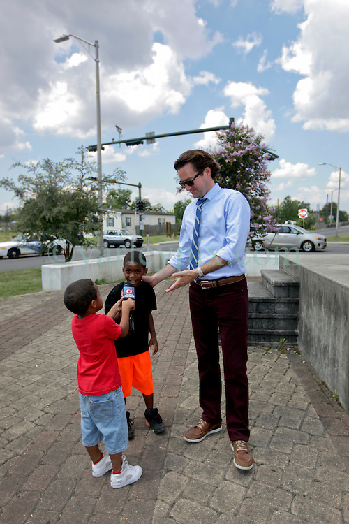 29 August 2015. Lower 9th Ward, New Orleans, Louisiana.<br /> Hurricane Katrina 10th Anniversary.<br /> WDSU's Travers Mackel finds himself a couple of young apprentices at the monument dedicated to the victims and survivors of the storm. <br /> Photo credit&copy;; Charlie Varley/varleypix.com.