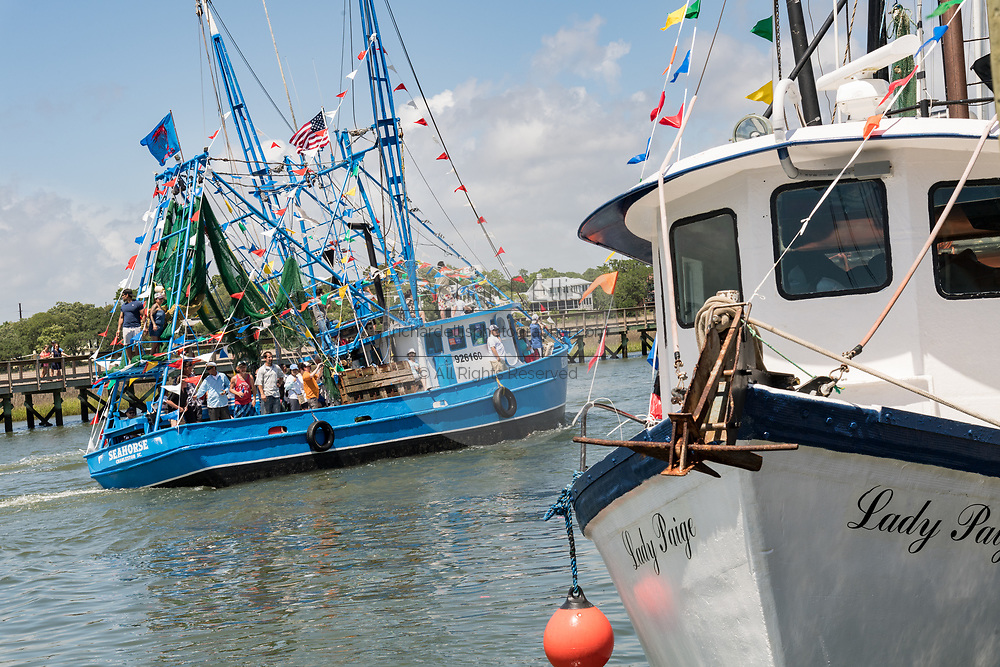 Decorated shrimp boats parade past the commercial fishing docks down Shem Creek during the annual Blessing of the Fleet signifying the start of the commercial shrimping season April 30, 2017 in Mount Pleasant, South Carolina. Coastal shrimping is part of the low country heritage but has been declining rapidly with rising costs and increased foreign competition.