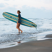 Surfer girl walking into the ocean carrying a surfboard.