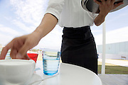 waiter serving coffee at an outdoor restaurant