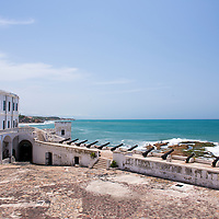View of historic cannons and the Atlantic Ocean at the Cape Coast Castle, a UNESCO World Heritage Site located along the Gold Coast of Ghana.