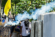 01 DECEMBER 2013 - BANGKOK, THAILAND: Anti-government rock throwers watch a tear gas cannister fly past them during a riot in Bangkok. Thousands of anti-government Thais confronted riot police at Phanitchayakan Intersection, where Rama V and Phitsanoluk Roads intersect, next to Government House (the office of the Prime Minister). Protestors threw rocks, cherry bombs, small explosives and Molotov cocktails at police who responded with waves of tear gas and chemical dispersal weapons. At least four people were killed at a university in suburban Bangkok when gangs of pro-government and anti-government demonstrators clashed. This is the most serious political violence in Thailand since 2010.    PHOTO BY JACK KURTZ