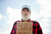 Portrait of a homeless person with sign