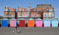 © Licensed to London News Pictures. 03/07/2018. Hove, UK. A young man kicks a football past colourful beach huts on the seafront at Hove, East Sussex on the south coast of England, as a heatwave continues across the UK. Photo credit: Ben Cawthra/LNP