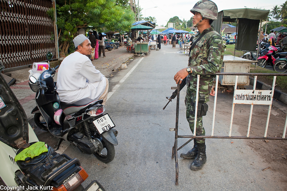 """Sept 26, 2009 -- PATTANI, THAILAND:  A Muslim man chats with a Thai soldier at a roadblock during a security operation near Krue Se Mosque in Pattani, Thailand, Sept. 26. Thailand's three southern most provinces; Yala, Pattani and Narathiwat are often called """"restive"""" and a decades long Muslim insurgency has gained traction recently. Nearly 4,000 people have been killed since 2004. The three southern provinces are under emergency control and there are more than 60,000 Thai military, police and paramilitary militia forces trying to keep the peace battling insurgents who favor car bombs and assassination.   Photo by Jack Kurtz / ZUMA Press"""