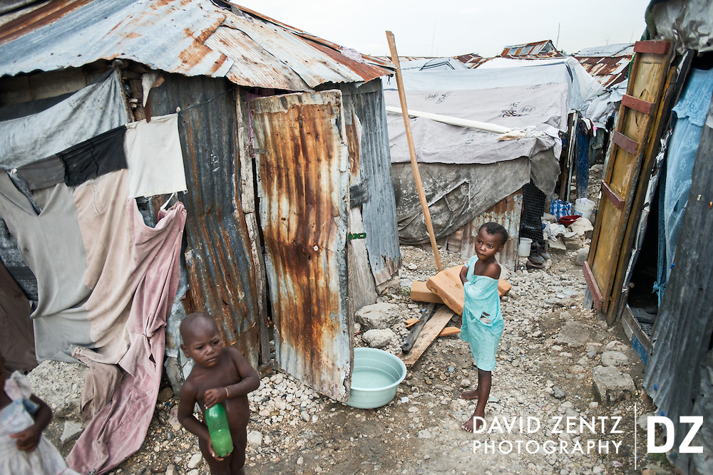 Children stand on a dirt path between ramshackle homes in the La Saline slum in Port au Prince, Haiti, on May 13, 2012.
