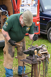 A farrier preparing a horseshoe for fitting at the Essex Country Show, Barleylands, Essex.