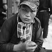 A Hmong man smokes a cigarette at the Sa Phin Market in Ha Giang, Vietnam's northernmost province, 22 June, 2007. As cities like Hanoi and Ho Chi Minh roar with Vietnam's economic boom, Ha Giang remains a quiet, serene and beautiful mountain backwater along the Chinese border.